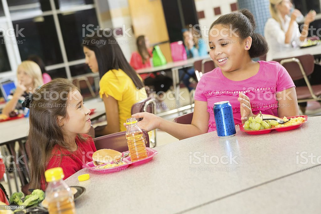 Elementary school students having lunch together in cafeteria royalty-free stock photo
