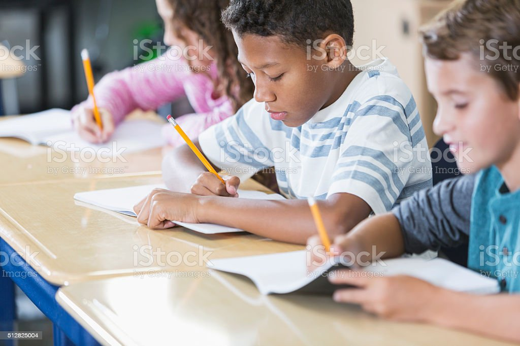 Elementary school students in class taking test stock photo