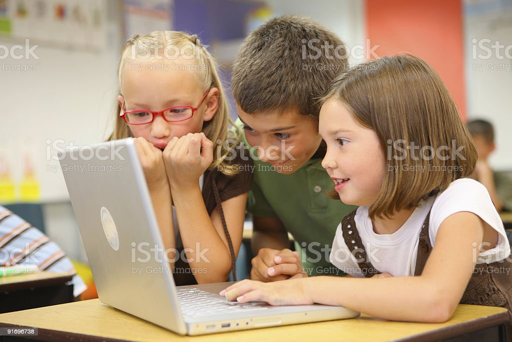 Elementary school students look at laptop computer stock photo