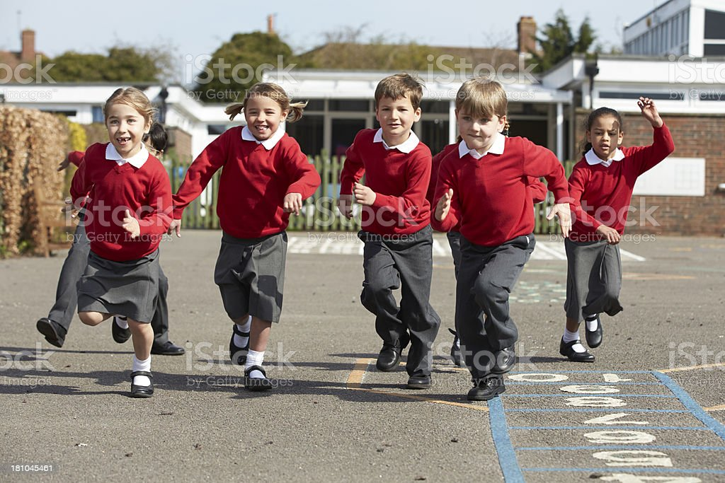 Elementary school students running in playground stock photo