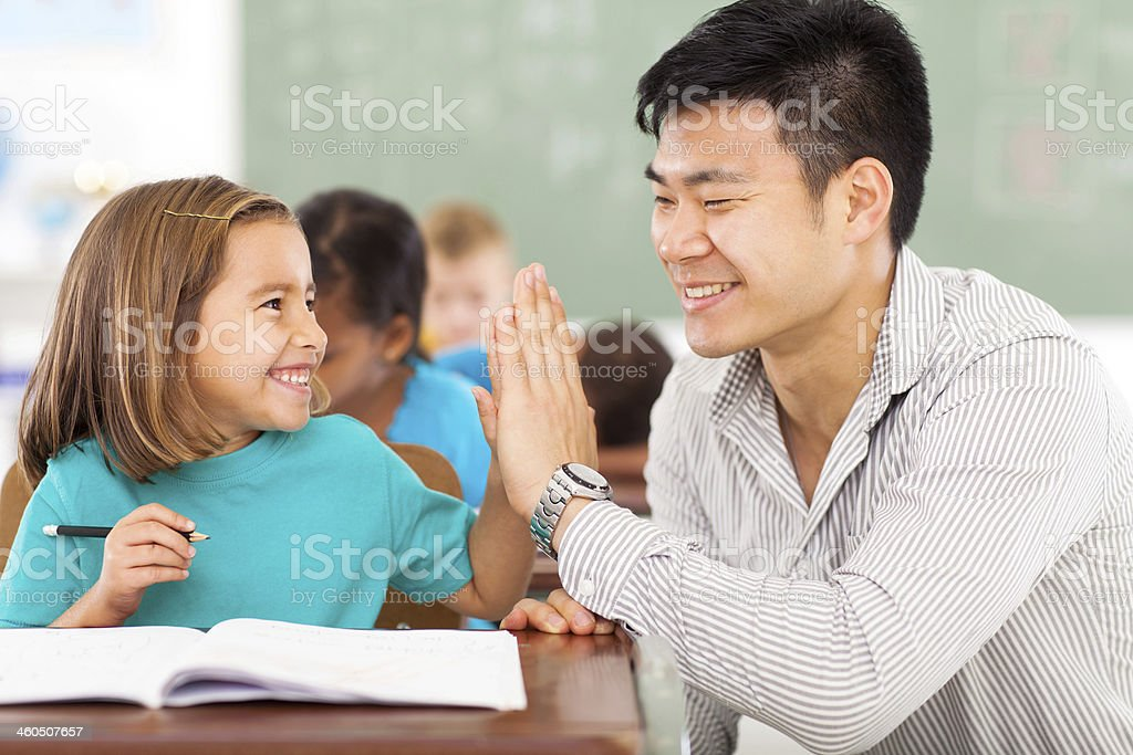 elementary school teacher and student high five stock photo
