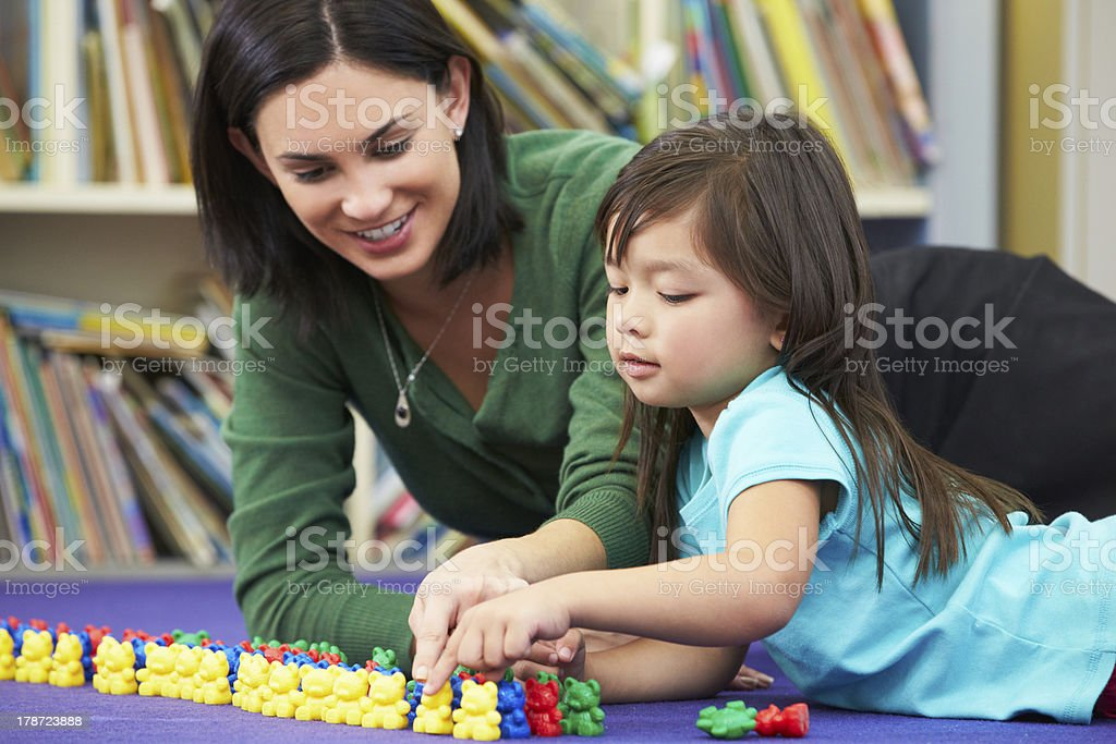 Elementary school teacher practicing counting with a student stock photo