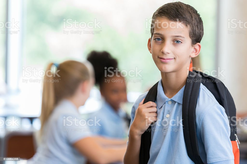 Elementary schoolboy waits for class to start stock photo
