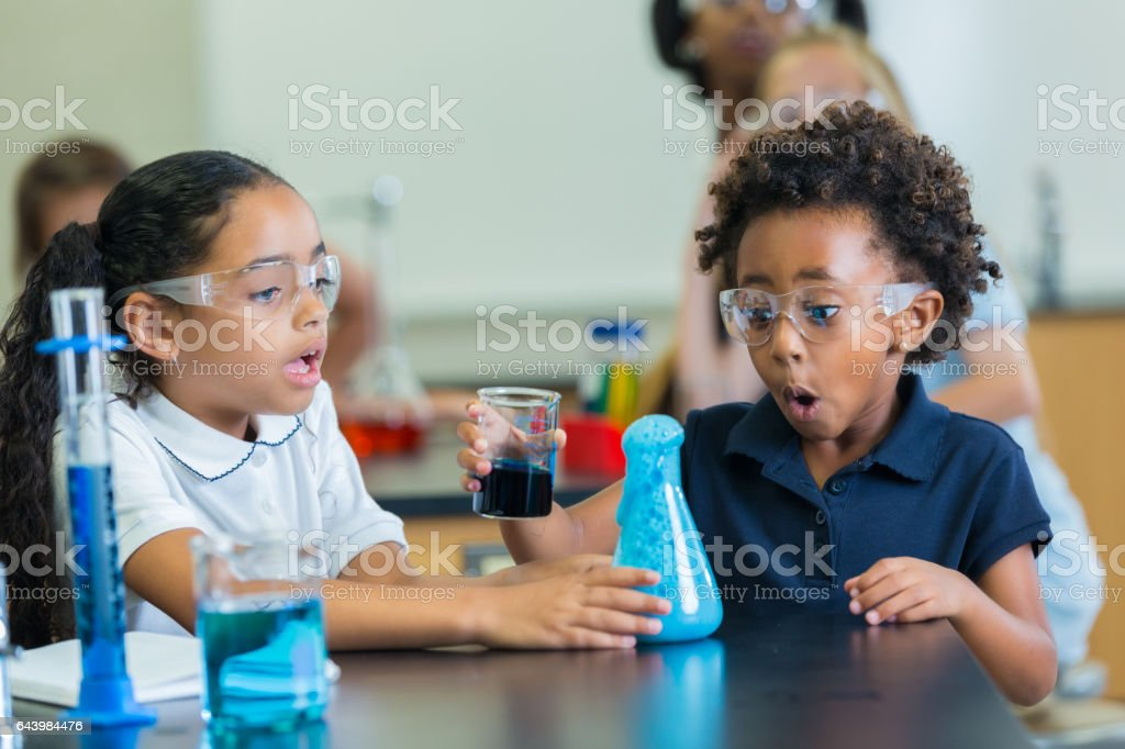 Elementary schoolgirls are surprised at chemical reaction in science class stock photo