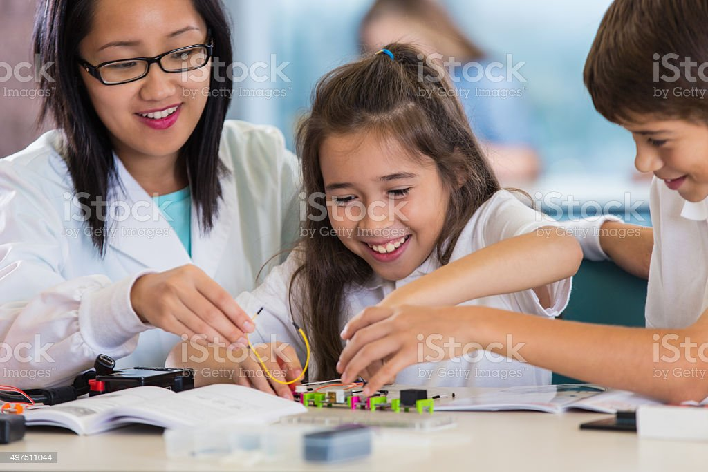 Elementary science teacher helping students build robot model stock photo
