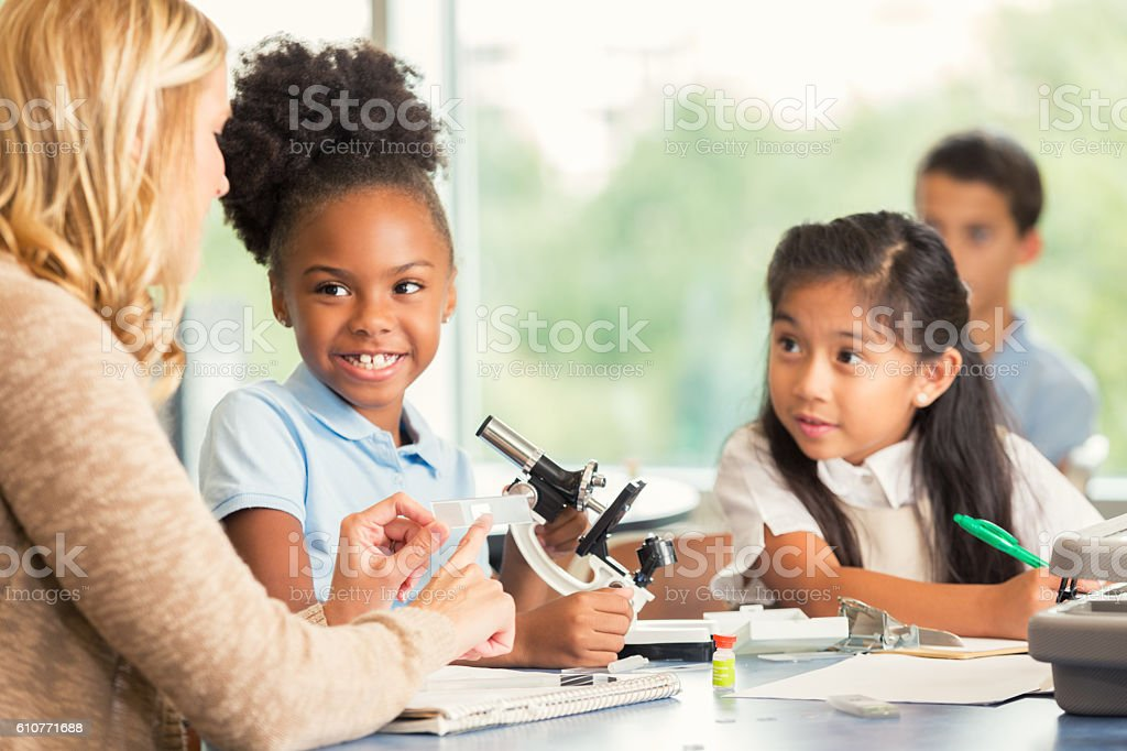 Elementary science teacher helps female students with project stock photo