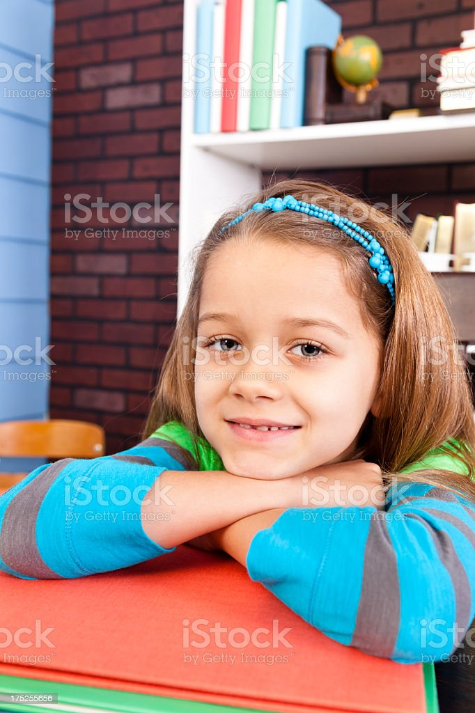 Elementary student, 7-8, girl with arms crossed stack library books royalty-free stock photo