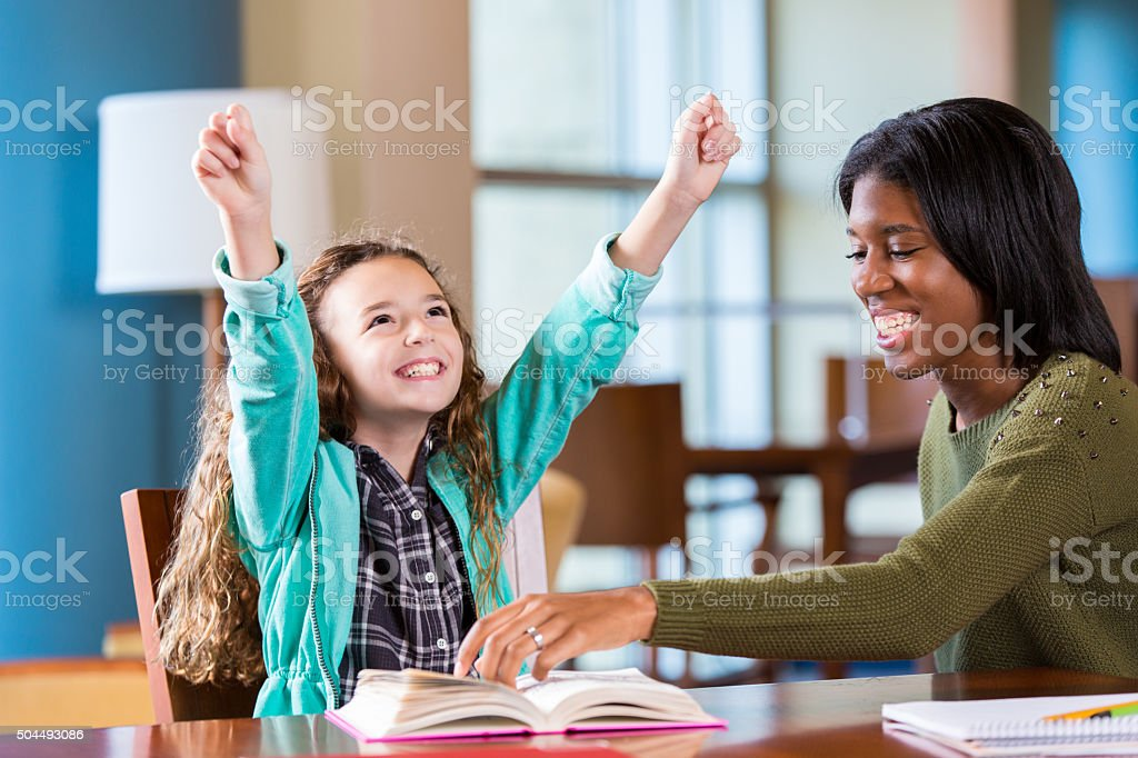Elementary student celebrating homework success while working with tutor stock photo