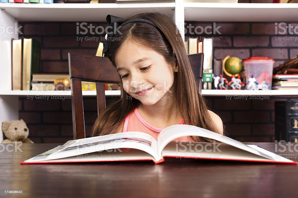 Elementary student girl 7-8 smiling reading book  school library royalty-free stock photo