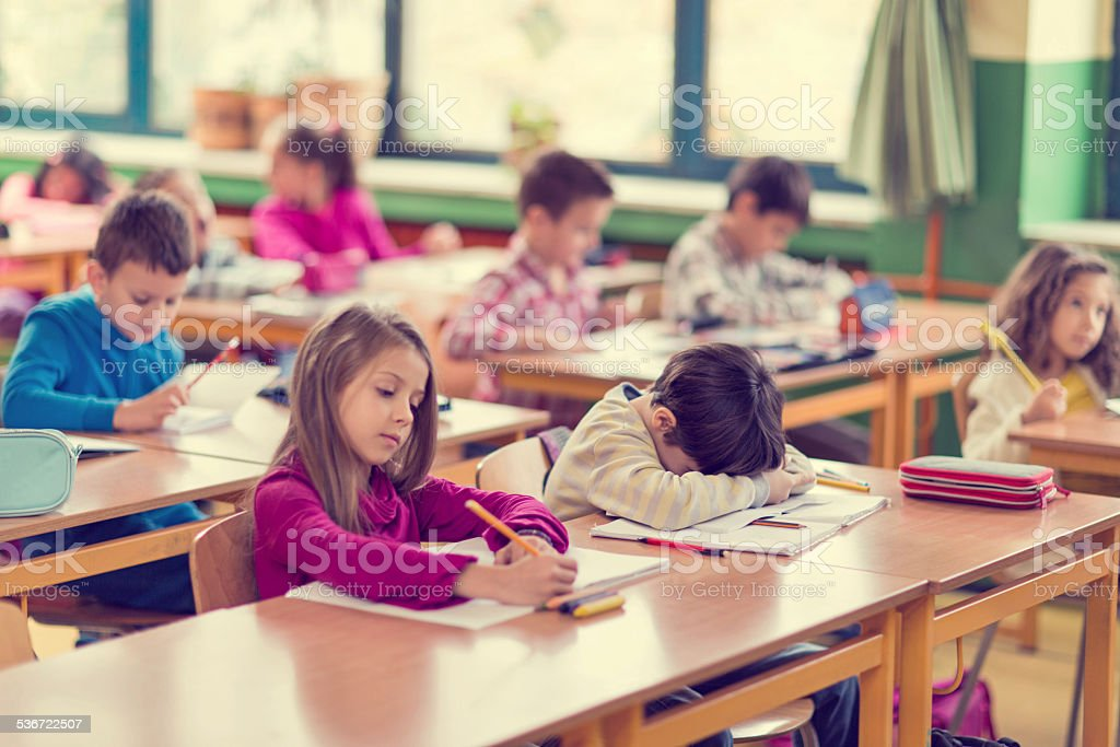 Elementary student napping in a classroom. stock photo