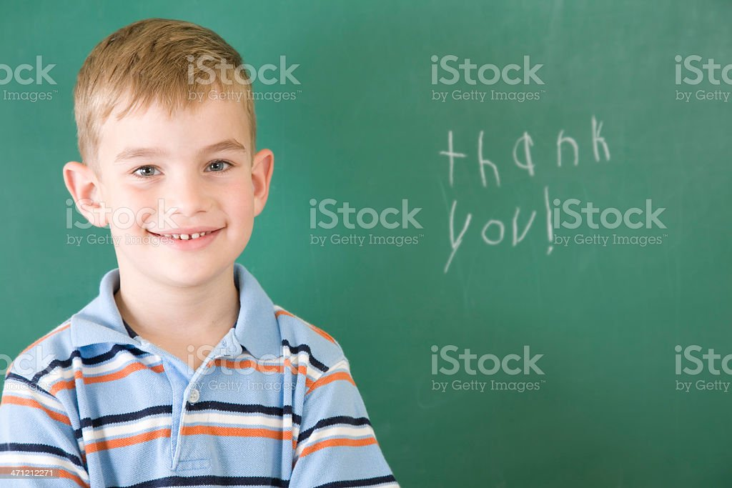 """Elementary Student Posing after Writing """"Thank You"""" on School Chalkboard royalty-free stock photo"""