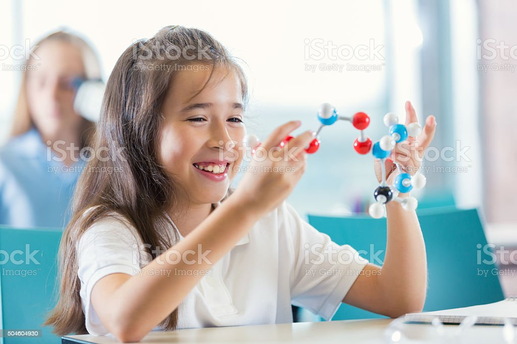 Elementary student studying molecule model in modern science class stock photo