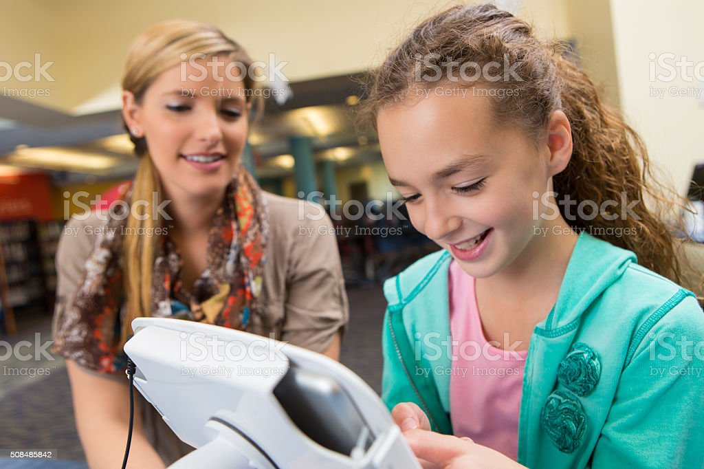 Elementary student using digital tablet in public library stock photo