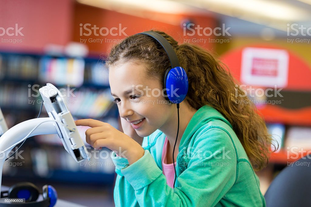 Elementary student using modern technology in library stock photo