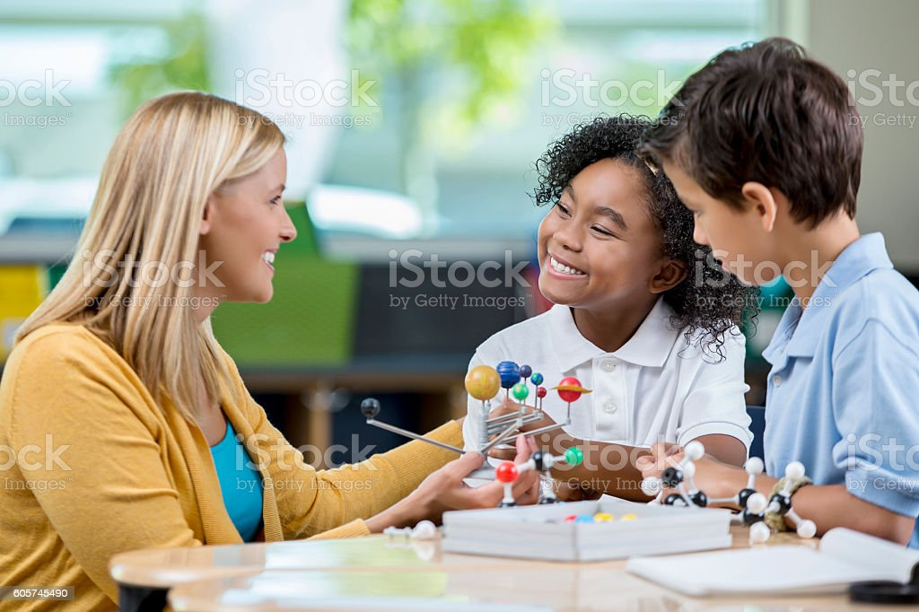 Elementary students and teacher studying the solar system in class stock photo