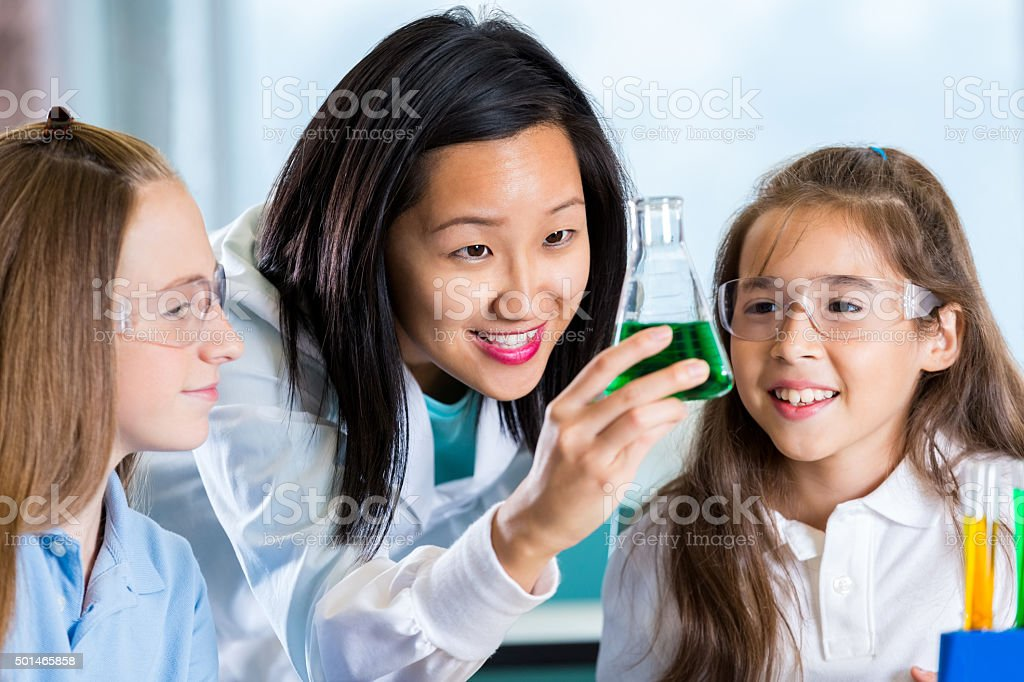 Elementary students and teacher watch chemical reaction in science class stock photo