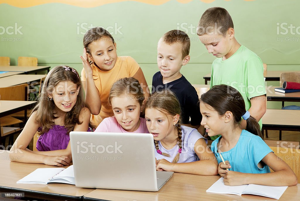 Elementary students having class with laptop royalty-free stock photo