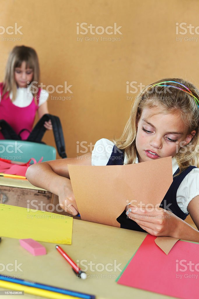 Elementary students in classroom setting working on projects stock photo