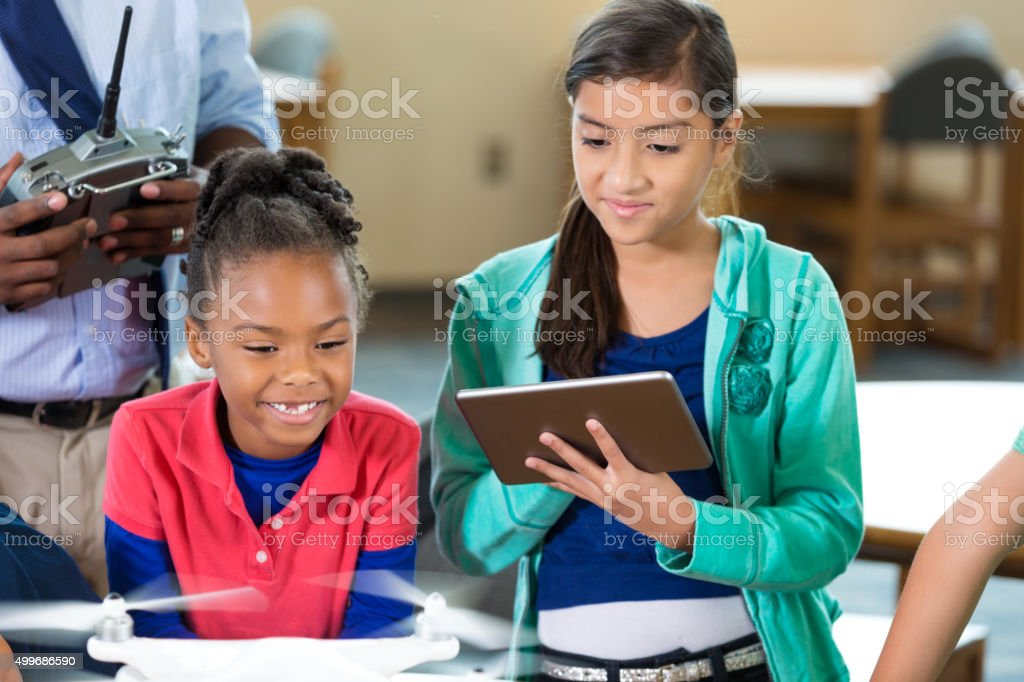 Elementary students learning about drone technology in class stock photo