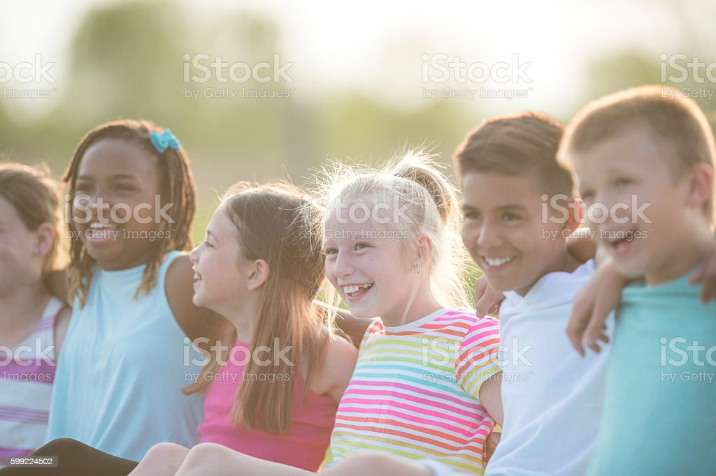 Elementary Students Sitting Together Outside stock photo