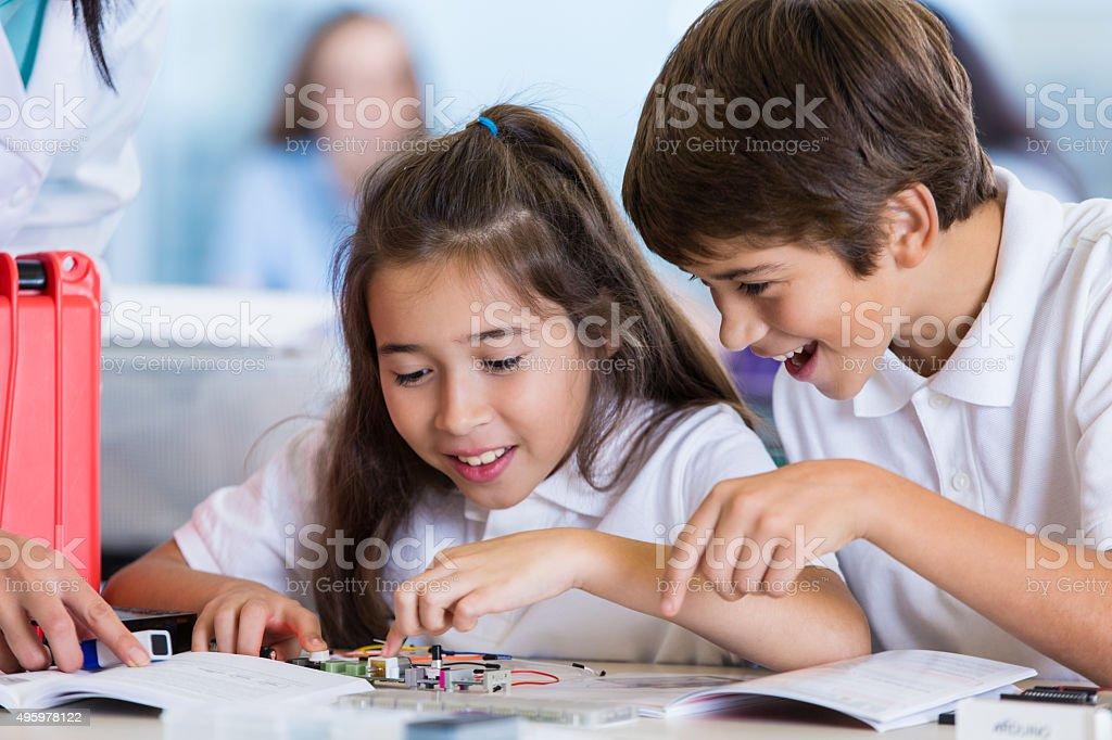 Elementary students studying robotics and technology stock photo