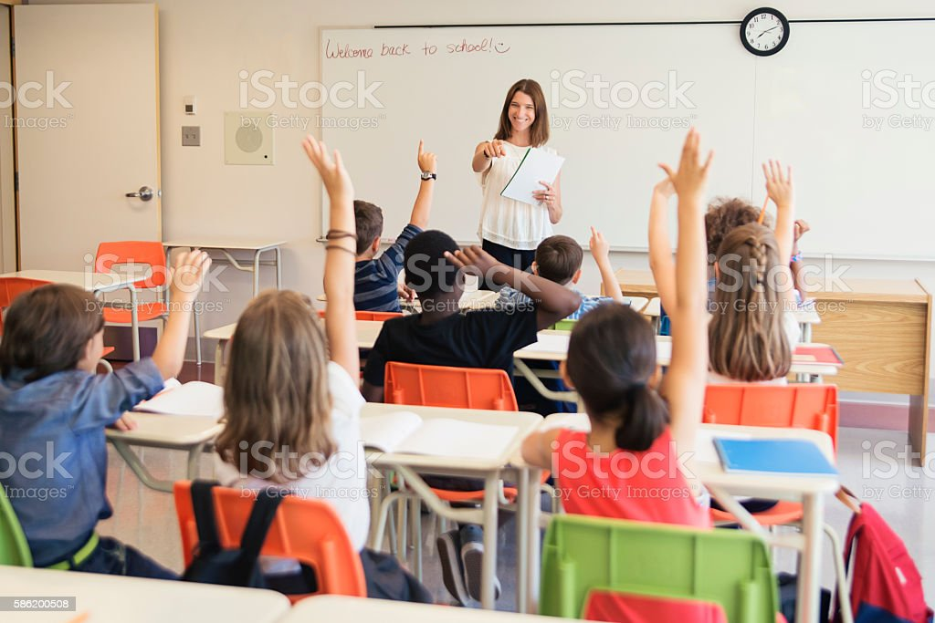 Elementary students with hand raised in class with teacher. stock photo