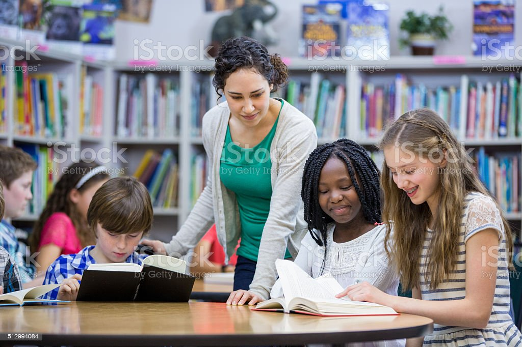 Elementary students working with teacher in library stock photo