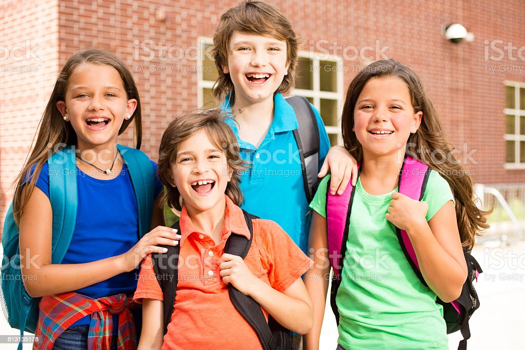 Elementary-age children, friends on school campus going back to school. stock photo