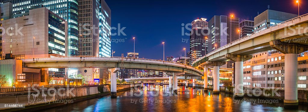 Elevated highways though futuristic neon skyscraper cityscape panorama Osaka Japan stock photo