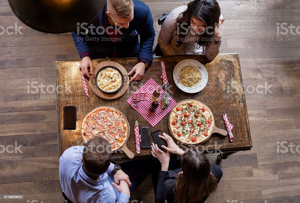 Elevated view of friends eating pizza stock photo