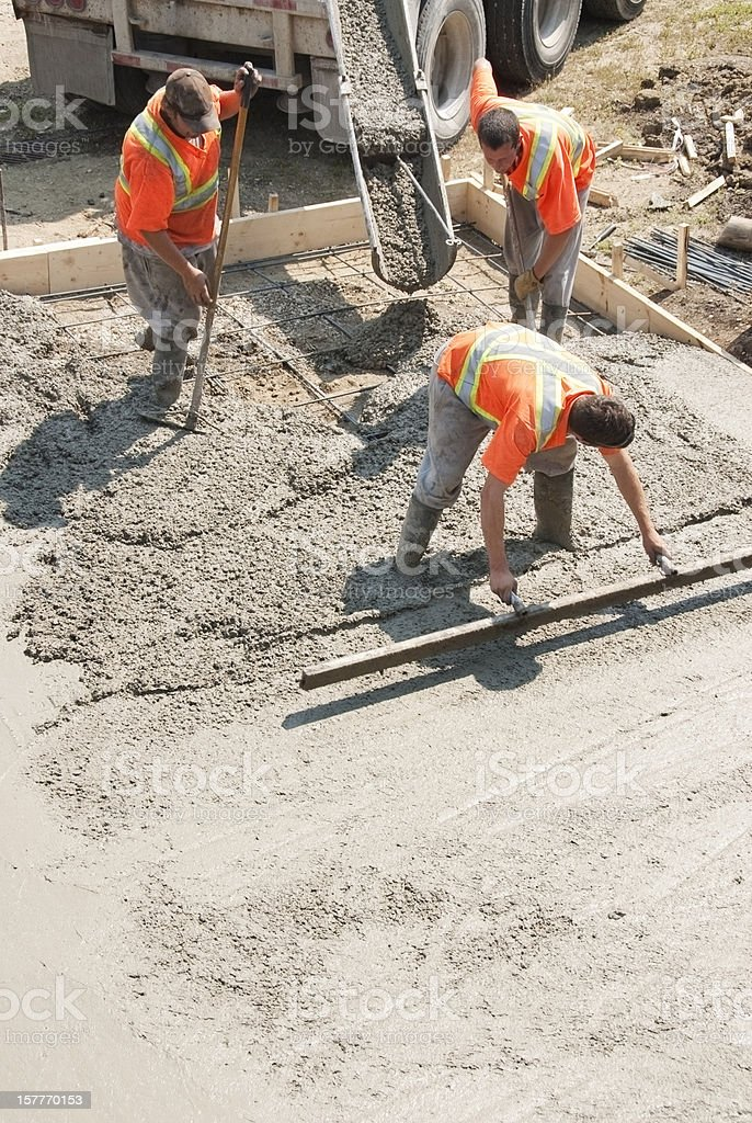 Elevated view of three builders working with concrete stock photo