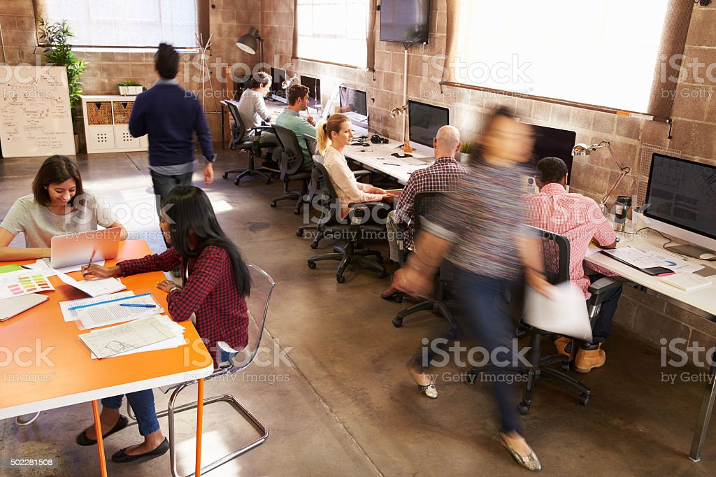Elevated View Of Workers In Busy Modern Design Office stock photo