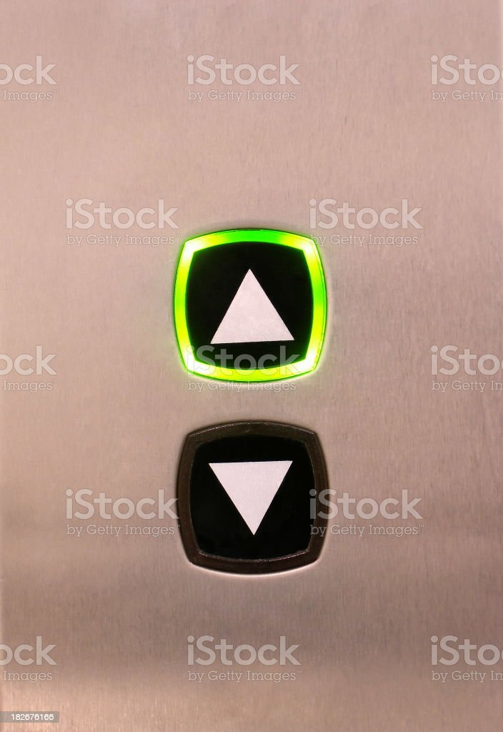 Elevator buttons on silver background, up button highlighted stock photo