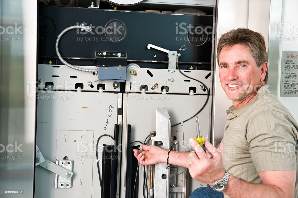 Elevator Tech using screwdriver to fix problem stock photo