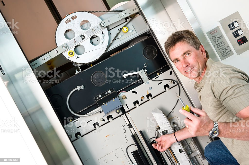 Elevator Tech using screwdriver to repair mechanical malfunction stock photo