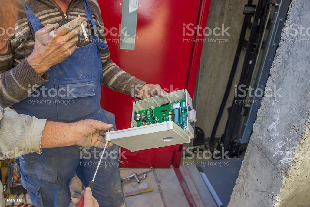 Elevator Technicians prepare the elevator control panel for inst stock photo
