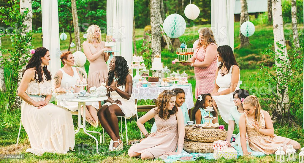 Eleven women having a garden party with dessert table stock photo