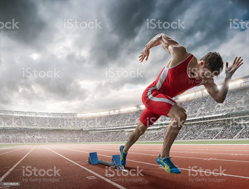 Elite 100m Runner Sprints From Blocks in Floodlit Stadium stock photo
