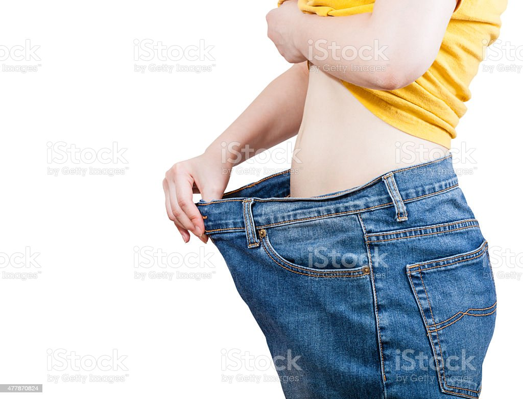 emaciated girl trying on large size old jeans stock photo