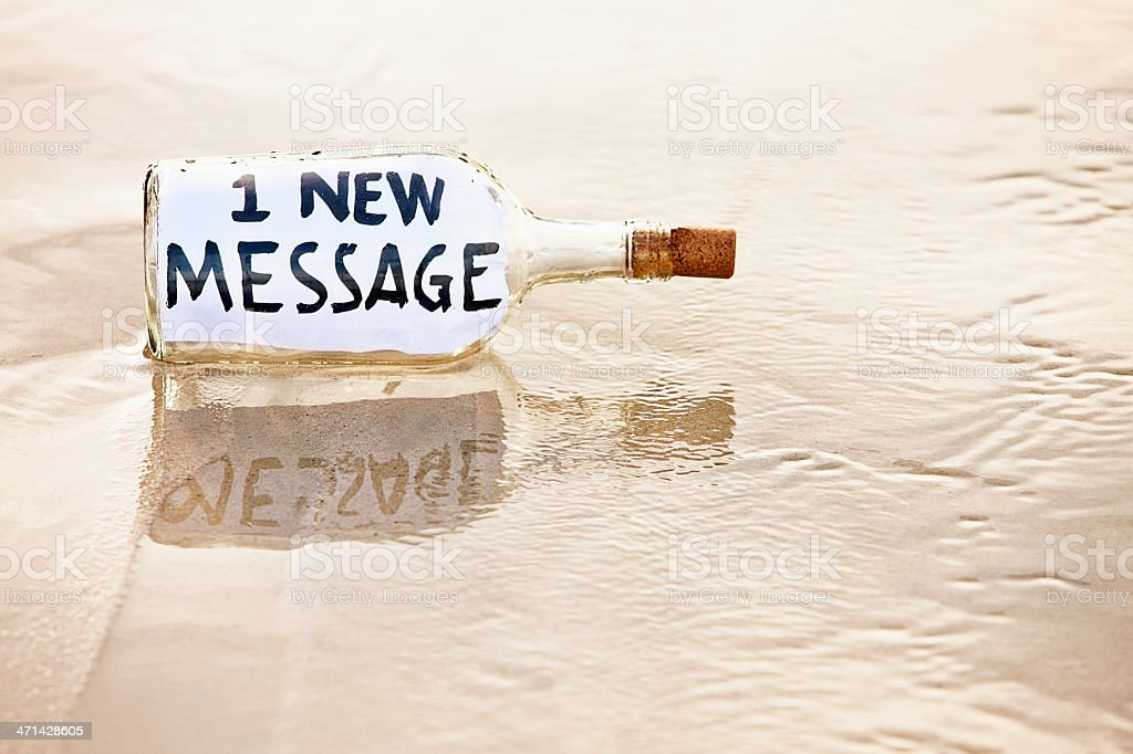 E-mail message from castaway in washed-up bottle on beach royalty-free stock photo