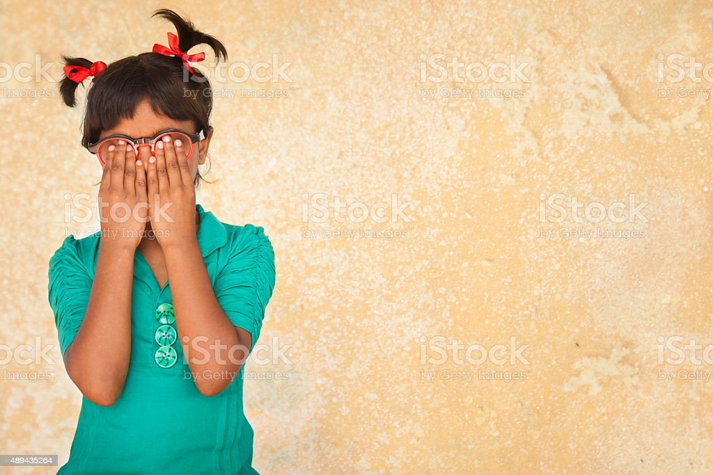 Embarassed, guilty, nervous little girl with hands covering face. stock photo