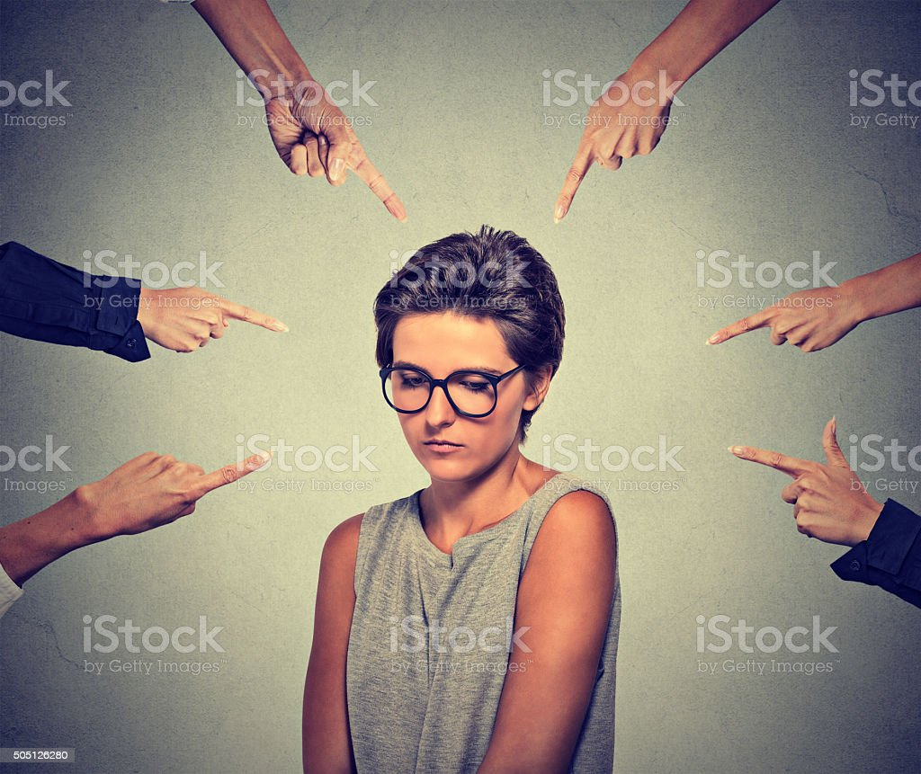 Embarrassed woman looking down many fingers pointing at her stock photo