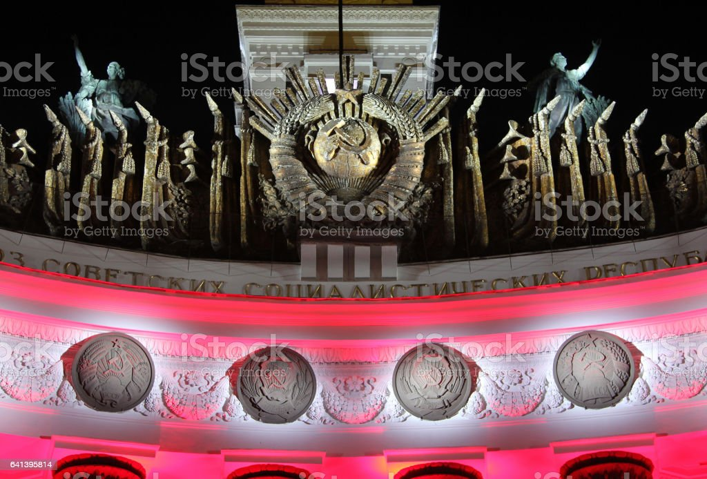 MOSCOW, RUSSIA - AUG 23, 2014: Emblem of USSR and four (of fifteen) republics in festive lighting - architectural detail of facade of pavilion at All Russian Exhibition center stock photo