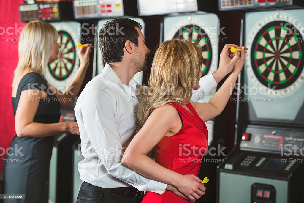 Embraced couple playing darts together. stock photo