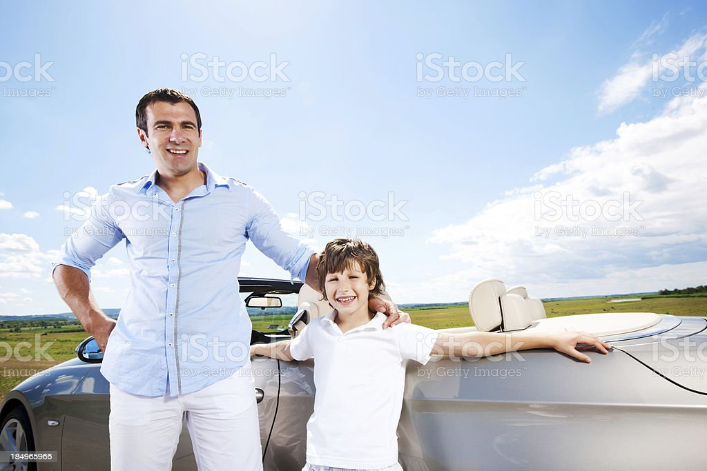 Embraced father and son near Convertible car. royalty-free stock photo