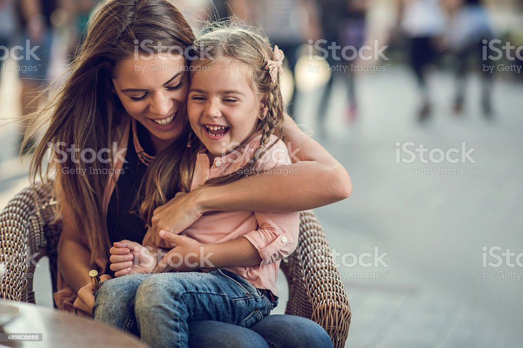 Embraced mother and daughter laughing and having fun outdoors. stock photo