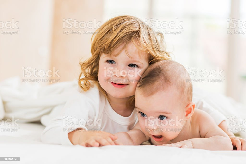 Embraced smiling little brothers lying down in bed. stock photo