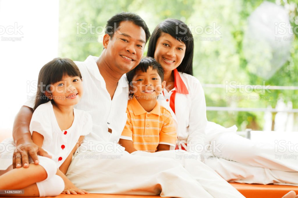 Embraced Thai family sitting on sofa in living room. royalty-free stock photo