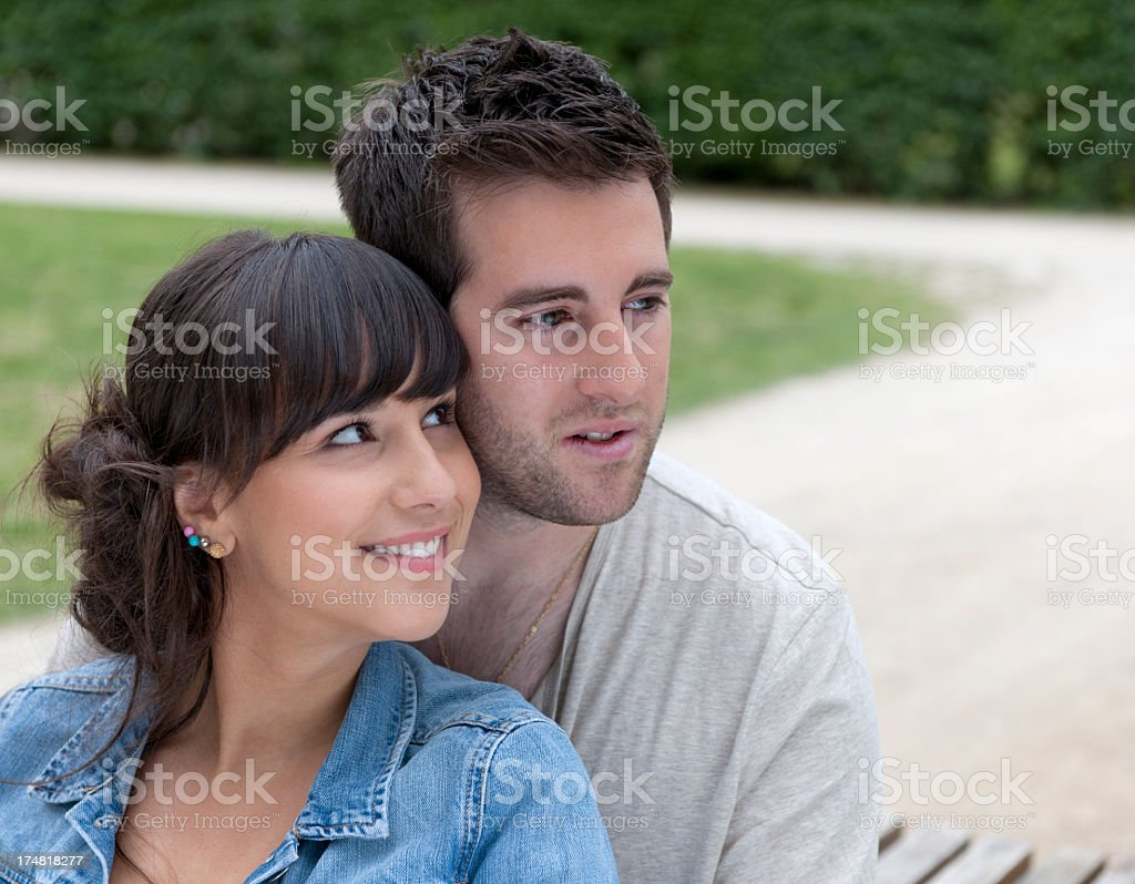 embracing happy young couple sitting on park bench royalty-free stock photo
