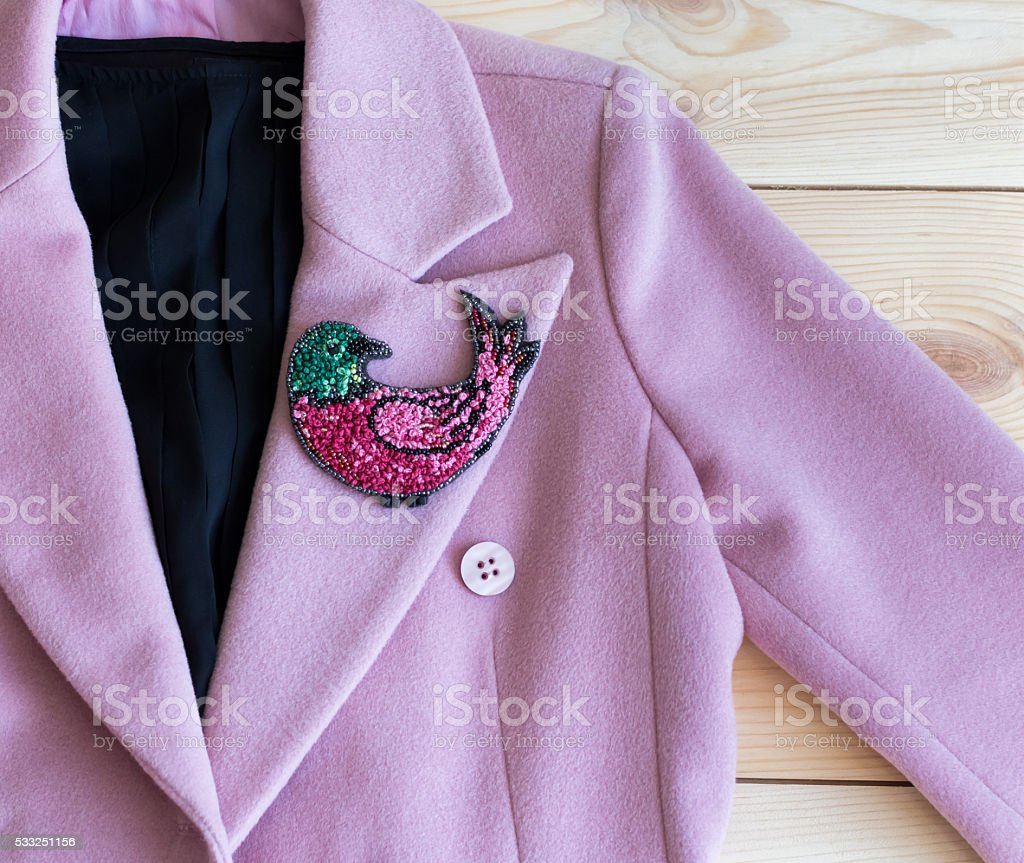 embroidered beaded brooch on a pink coat stock photo